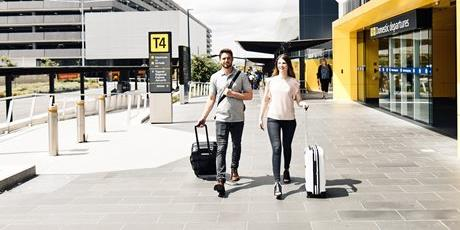 Couple walk with their luggage at airport. Buy extra baggage when you book your Jetstar flight and save on airport prices.