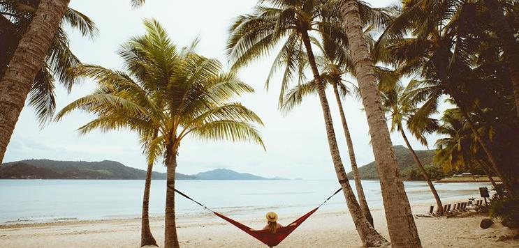 A woman sits on a hammock overlooking the beach in the Whitsundays.